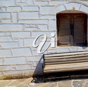 and stone pavement in the greece island of paros old bench near a brick antique wall