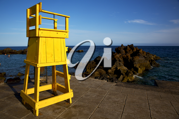 yellow lifeguard chair cabin  in spain  lanzarote  rock stone sky cloud beach  water  musk pond  coastline and summer