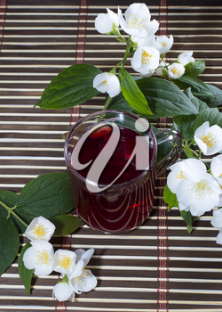 the transparent mug of red drink decorated with a flower