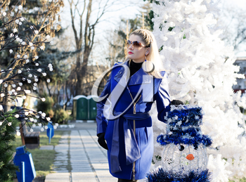 the beautiful woman in a blue coat at a fir-tree and a snowman, a subject the woman and holidays Christmas and New Year
