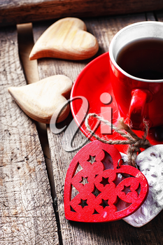 Red Cup with black coffee and two carved decorative wooden heart.Selective focus