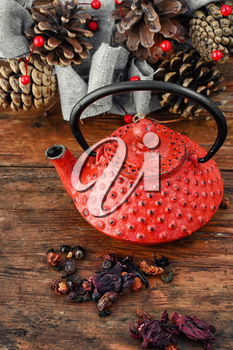 Red metal teapot,tea leaves and autumn pine cones