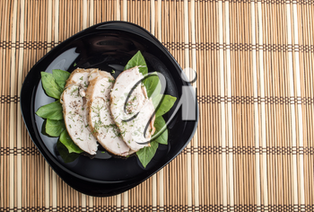 Foodstyle background with three slices of roasted chicken on a black plate decorated with green leaves of basil on a striped bamboo mat