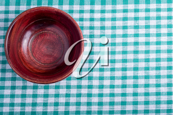 Top view of the surface of the table with checkered tablecloth, on which stands a small empty wooden bowl