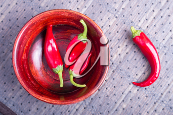 Fruits chilli hot red pepper in a brown wooden bowl on a fabric background