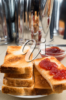 Toasted slices of bread with strawberry jam on the table with kitchen utensils with a blurred background