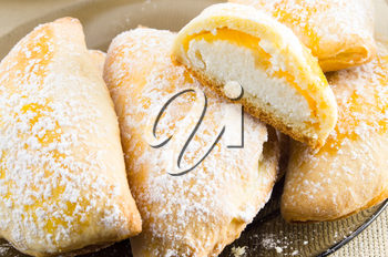 Sweet cakes with curd sprinkled with powdered sugar on a dark plate with shallow depth of field