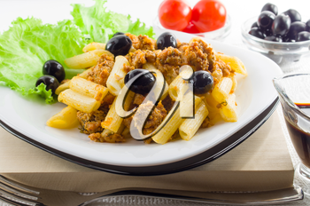 Italian pasta penne with bolognese sauce, beef meat and olives on a white plate closeup