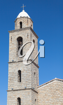 Bell tower of Propriano church, gray stone facade on a blue sky background