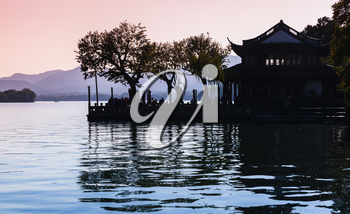 Black trees silhouette and traditional Chinese buildings on the coast of West Lake. Famous public park in Hangzhou city, China