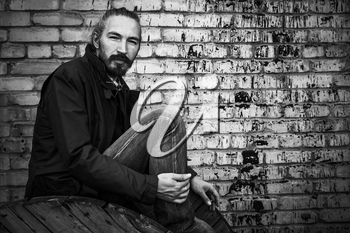Young bearded man sitting near grungy brick wall, outdoor black and white portrait