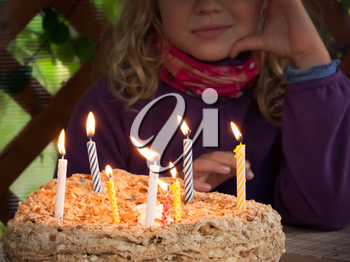 Colorful candles on  birthday cake in the dark. Selective focus on fire
