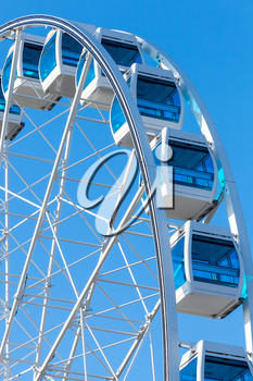 Ferris wheel over clear blue sky background, vertical photo