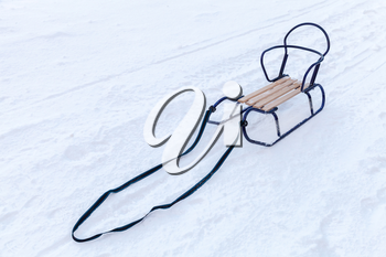 Small metal sled with wooden seat standing in the snow