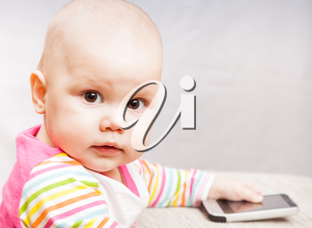 Little baby in colorful striped clothing with mobile phone looks in camera