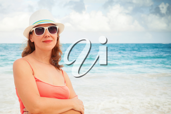 Young happy Caucasian woman in red dress, and sunglasses and white hat. Summer outdoor portrait on the ocean coast. Toned photo with warming filter effect