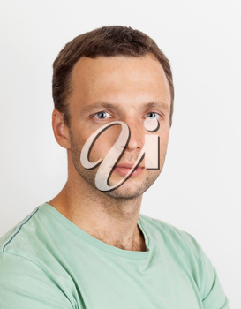 Young Caucasian man in casual clothing, studio portrait over light gray background
