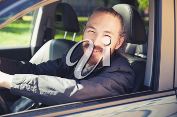 Smiling Asian man as a driver of modern Japanese suv, outdoor portrait in open car window, vintage stylized photo with tonal correction photo filter