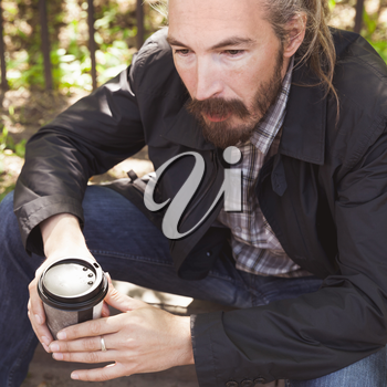 Bearded Asian man with coffee in paper cup, outdoor square portrait with selective focus