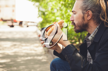 Bearded Asian man eating hot dog with coffee in summer park, outdoor profile portrait with selective focus