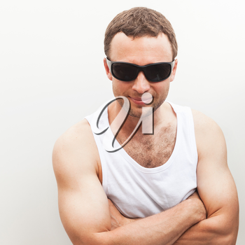 Portrait of Young sporty Caucasian man in white shirt and black sunglasses