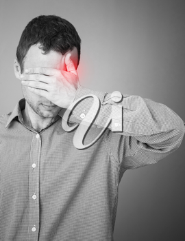 Young adult man with headache. Black and white stylized photo with red local ache spot