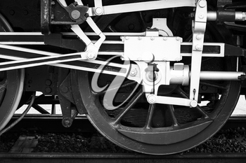 Wheels of steam locomotive with the power parts, stylized black and white photo