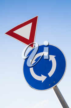 Triangle Give way and round Traffic roundabout road signs on one metal pole over blue sky