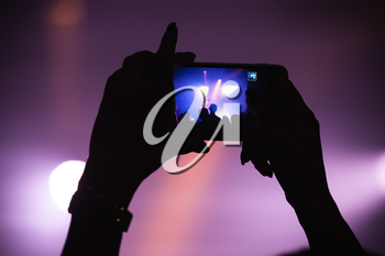 Hands of woman taking photo on her smartphone camera, rock music concert, closeup