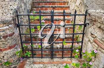 Closed black metal gate to the red brick stairway going up