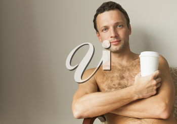 Portrait of young European man sitting with white paper cup of Coffee
