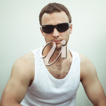 Portrait of Young sporty serious European man in white shirt and black sunglasses, vintage toned square photo