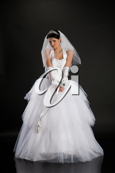 Young beautiful woman in a wedding dress on a studio background