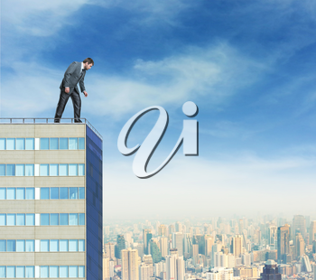 Businessman looks down from a high building against the city