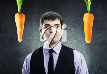 Two carrots and businessman between