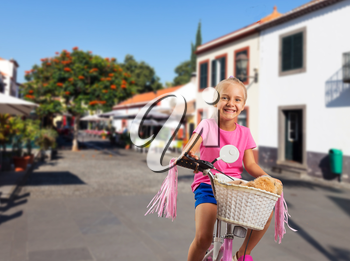 Smiling little girl cycling on pink bike on the street