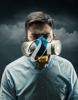 Young man in a gas-mask with atmospheric pollution