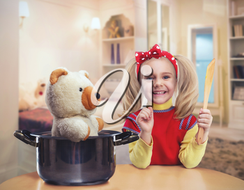 Happy little girl in the kitchen plays with her bear