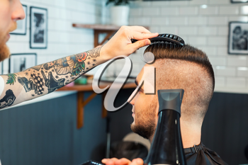 Young man having hair dress, barber working with hair dryer in dark room