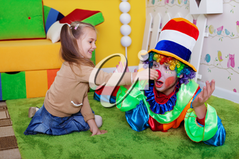 Smiling girl and the clown play on a carpet in the nursery. Colourful sofa, nesting box and fence on the background.