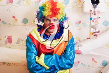 Portrait of angry clown with rainbow colored hairstyle and makeup. Decorative nesting box with input in form of heart on the background.