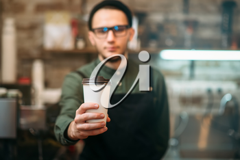 Barman in black apron stretches plastic cup of coffee in hands.