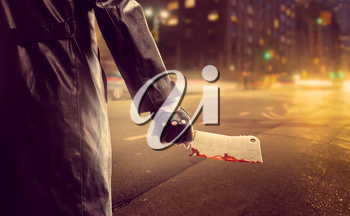 Serial murderer standing on road and holding bloody meat cleaver in hand. Night city on background.