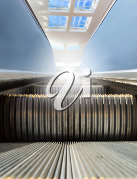 Modern escalator at sunny day with window at the background.