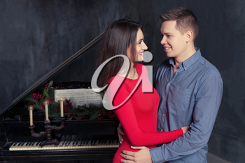 Beautiful young loving couple embraces,retro piano on background