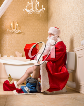 Santa Claus with his pants down sitting on the toilet and holding gift box in hands. Christmas humor