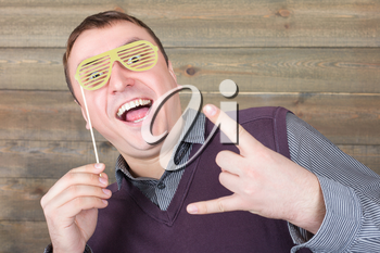 Playful young man with funny hipster sunglasses on a stick, wooden background. Fun photo props and accessories for shoots