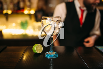 Attractive cocktail and lime on wooden counter. Advertising of alcoholic beverages