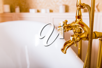 Rich gold faucet and white bath in the bathroom. Luxury sanitary equipment