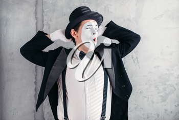Pantomime artist with makeup mask. Mime in suit, gloves and hat. April fools day concept